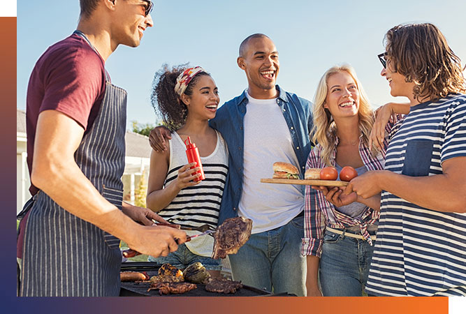 Group of friends laughing and grilling food